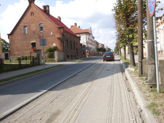 Ulica. Pocztowa w Więcborku z sypiącymi się półwiecznymi drewnianymi i betonowymi słupami oświetleniowymi Enea - foto Tomasz Roman Bracka